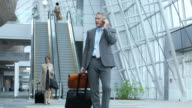 WS Businessman Talking on Cell Phone in Airport Lobby with Luggage / Virginia Beach, Virginia, United States