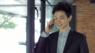 Businessman talking on his mobile phone indoor office , dolly shot left to right and tilt down