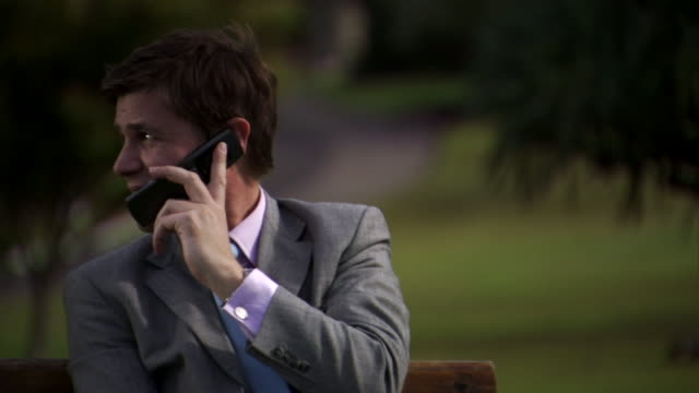 CU, Businessman talking on mobile phone in park, Sydney, Australia