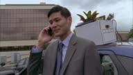 MS Businessman talking on phone in car park, Kansas City, Missouri, USA