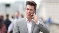 Businessman talking on smartphone on crowded street