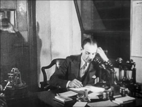 B/W 1929 businessman talking on telephone in office / newsreel