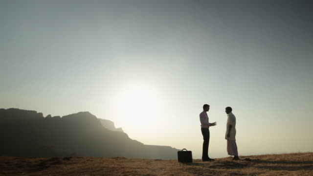 Businessman talking with a senior man on the cliff of mountain