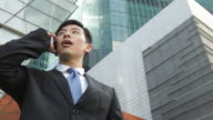 A businessman talks on a cell phone and pauses in front of modern skyscrapers.