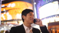 A businessman talks on a cell phone while standing in a bright shopping district.