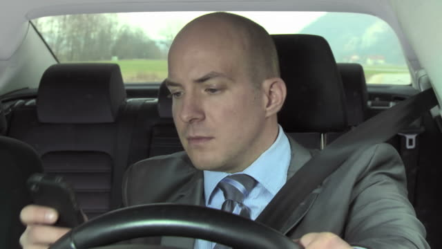 HD: Businessman Text Messaging While Driving