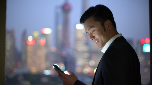 CU businessman texting by a window, Shanghai, China