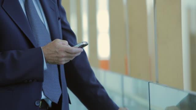 CU TU Businessman texting in office hallway / Vancouver, British Columbia, Canada