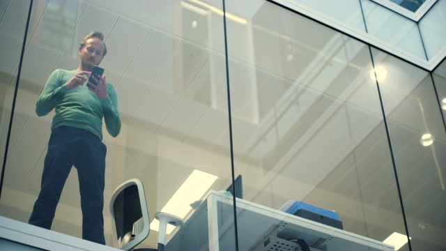 WS of businessman texting on cell phone by window in modern office