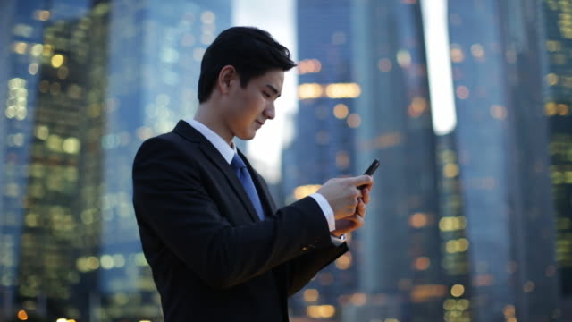 MS businessman texting on phone in front of buildings in the evening.