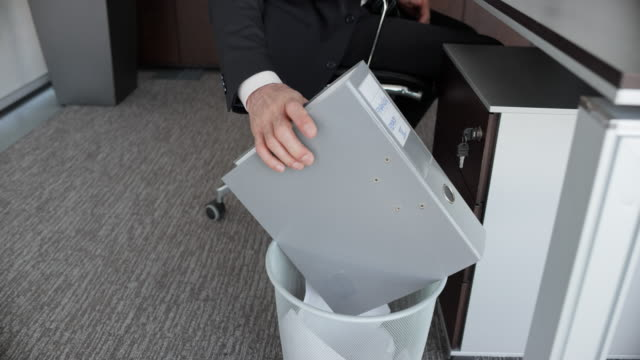 SLO MO DS Businessman throwing a ring binder into the trash