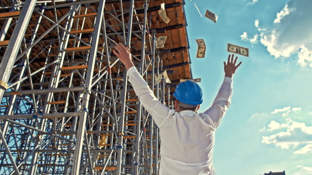 SLO MO Businessman throwing money at the construction site