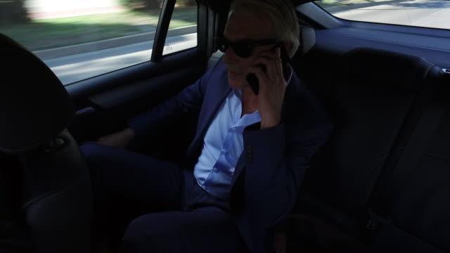 Affärsman färdas i baksätet på en bil och med smartphone