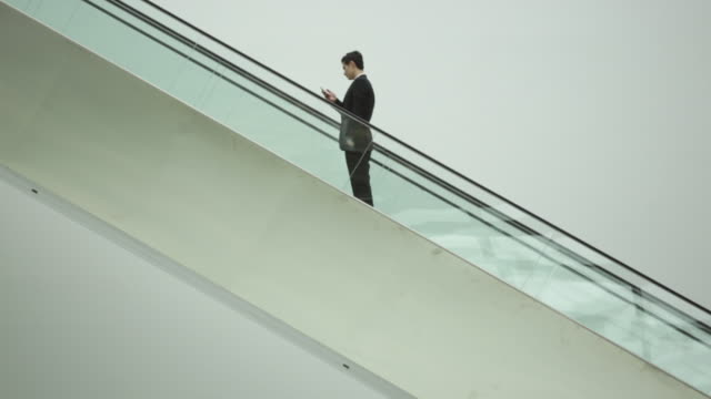 MS Businessman travelling up escalator.