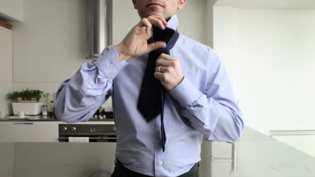 Businessman tying tie