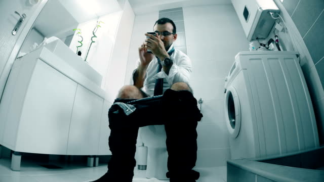 businessman uses a smart phone in the bathroom