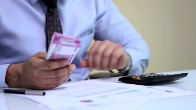 Businessman using a calculator and counting indian two thousand banknotes
