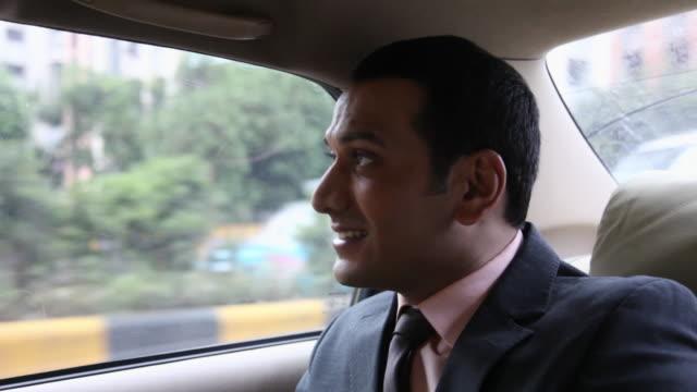 Businessman using a mobile phone in a car, Mumbai, Maharashtra, India
