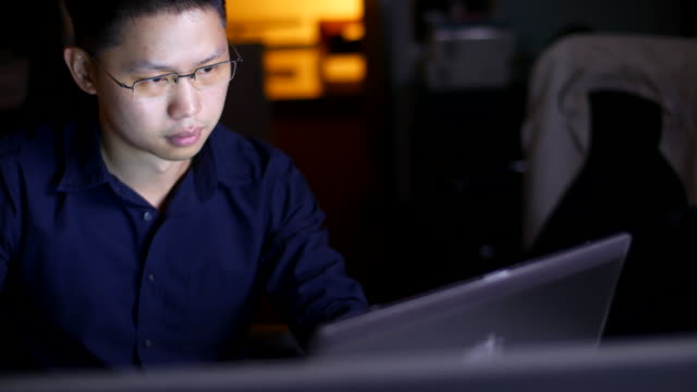 Businessman using computer in office at night