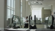 Businessman using digital tablet and ascending on escalator then tripping in office lobby / Provo, Utah, United States,