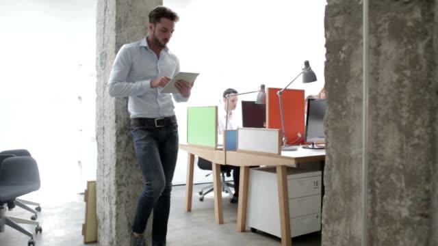 HD: Businessman using digital tablet in office.