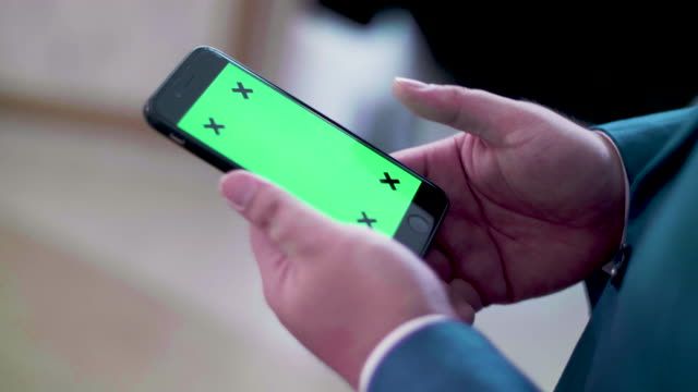 CU : Businessman Using Green Screen On Mobile Phone