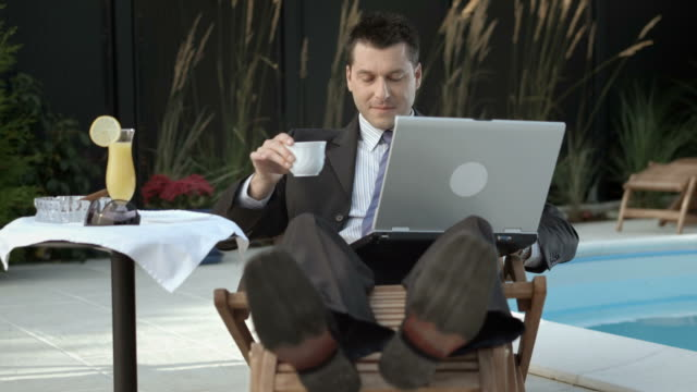 HD DOLLY: Businessman Using Laptop By The Pool