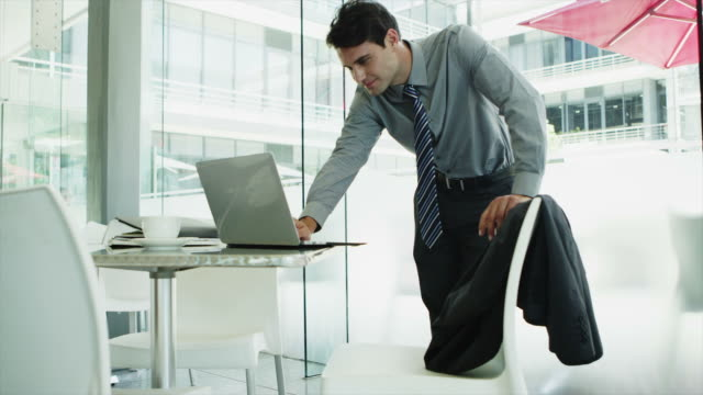 MS of businessman using laptop on office