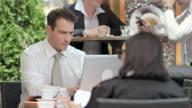 HD: Businessman Using Laptop On The Sidewalk Cafe