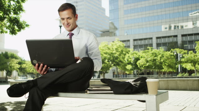 MS DS of businessman using laptop outdoors