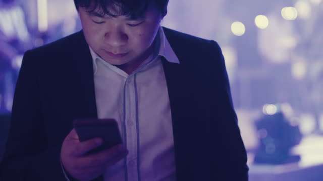 Businessman Using Mobile Phone at a Party Event