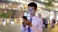 Businessman using mobile phone at night