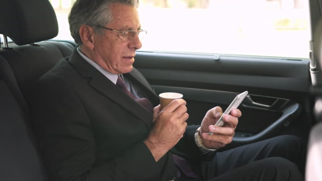 Businessman using smart phone and drinking coffee in a car