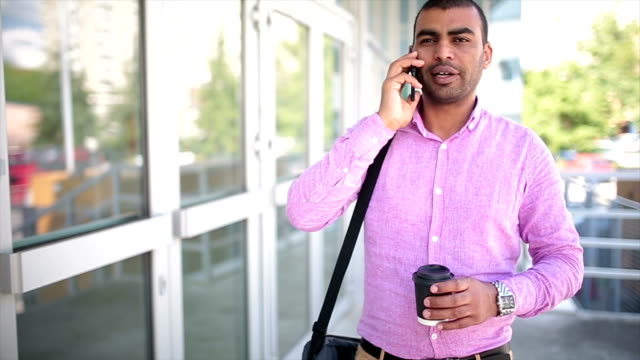 Businessman using smartphone and holding paper cup with coffee in a urban scene