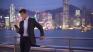 WS businessman using smartphone at night in Hong Kong