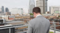 Businessman using smartphone looking out at London city skyline