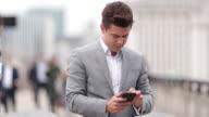 Businessman using smartphone on crowded street