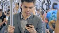 Businessman using smartphone on train,Close-up