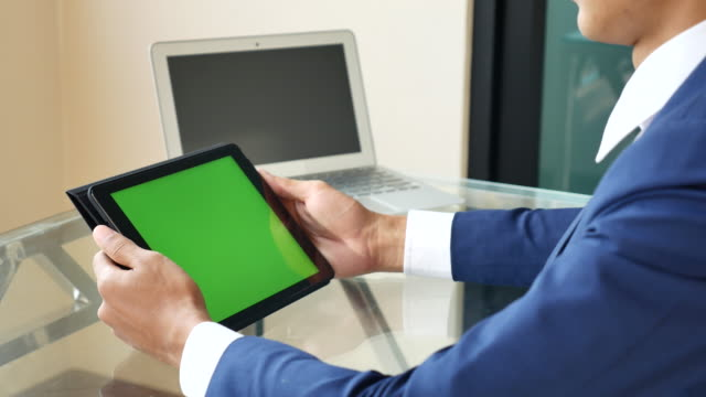 Businessman using Tablet PC with green screen