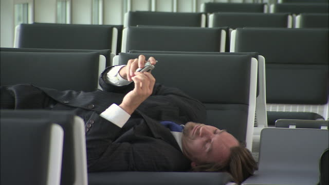MS Businessman waking up in airport lounge and talking on mobile phone while lying across chairs / Munich, Germany