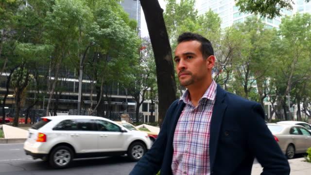 MS TS Businessman walking down sidewalk of city street