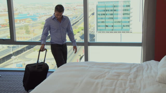WS PAN Businessman walking into hotel room and lying on bed / Cape Town, Cape Town, South Africa