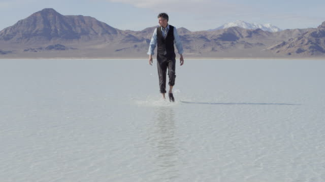 MS Businessman walking through shallow water in desolate landscape
