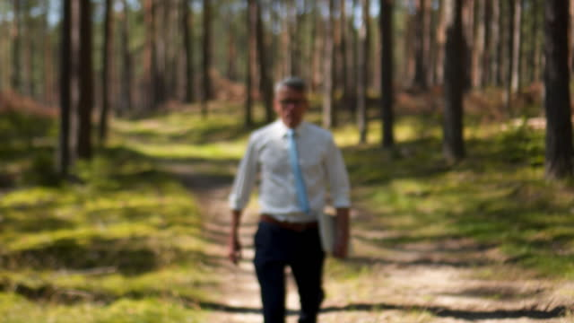 Businessman walking through the forest