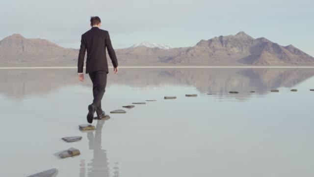MS PAN Businessman walking to end of stone path in lake