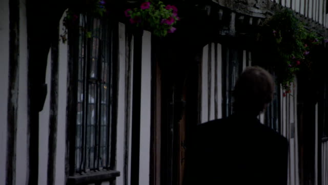 A businessman walks past a shop. Available in HD.