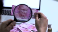 Businessman watcing indian two thousand bankbote through Magnifying glass