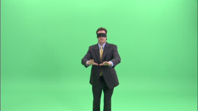 MS,  Businessman wearing blindfold walking aimlessly in studio