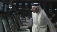 MS Businessman wearing keffiyeh and working in television studio control room / Culver City, California, USA