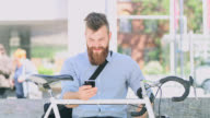 DS Businessman with beard using a smartphone in front of the office building